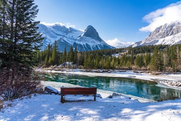 Bow river w zimowy słoneczny dzień. pokryte śniegiem pasmo górskie mount rundle w tle.