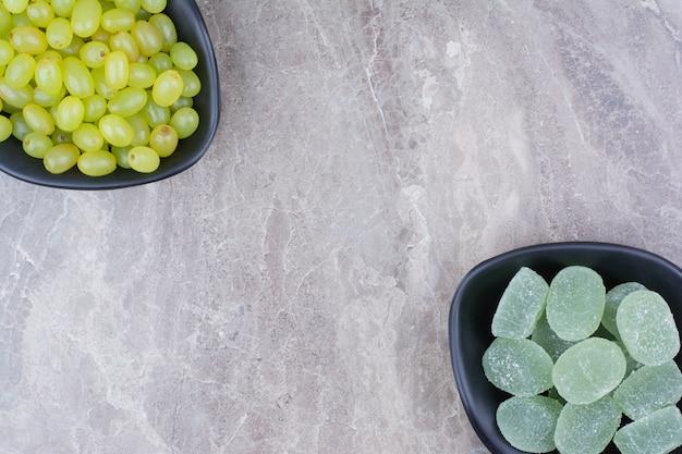 Bowlof winogron i cukierki marmolady na kamiennym tle.