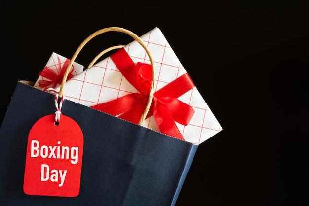 Boxing day tekst sprzedaży na czarnej etykiecie z torby na zakupy i pudełko na czarnym tle