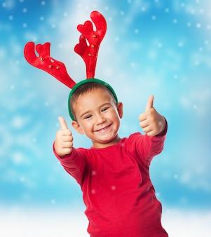 Boy noszenie rogi reniferów z christmas tle