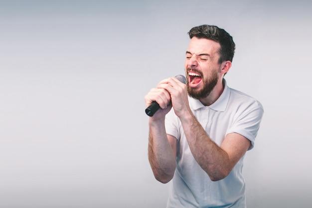 Boy rocking out. wizerunek przystojny mężczyzna śpiewa mikrofon, odizolowywający na świetle. emocjonalny portret atrakcyjnego faceta na szarej ścianie. nerd ma na sobie okulary
