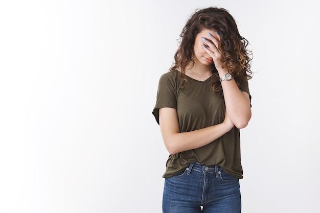 Boże, dlaczego ja. portret zirytowany znudzony wkurzony młoda ormiańska kobieta sprawia, że twarz palmy ukrywa twarz zamknij oczy pochyla głowę w dół zmartwiony, zmęczony wyjaśnianiem prostych zadań, stojąc na białym tle