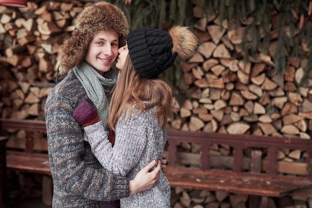Boże narodzenia i pary pojęcie - uśmiechnięty mężczyzna i kobieta w kapeluszach i szaliku ściska nad drewnianym dom na wsi i śniegu tłem