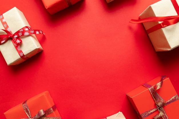 Boże narodzenia wykonują ręcznie prezentów handmade pudełka na czerwonego tła odgórnym widoku. motyw wakacji zimowych. leżał płasko.