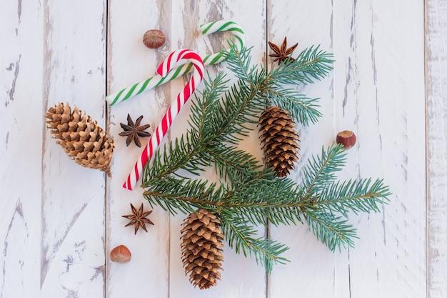 Boże narodzenie banckground z gałęzi sosny, szyszki i laski cukierków na rustykalne deski drewniane.