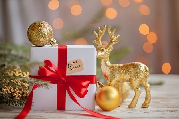 Boże narodzenie białe pudełko lub prezent ze złotymi kulkami i jelenia dla tajnego świętego mikołaja na drewnianym stole.
