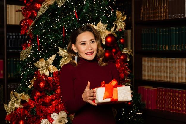 Boże narodzenie, boże narodzenie, zima, koncepcja szczęścia - uśmiechnięta kobieta w ubraniach świętego mikołaja z wieloma pudełkami prezentowymi