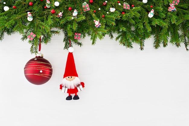 Boże narodzenie bożenarodzeniowa jedlinowa gałąź z santa i czerwoną bożenarodzeniową piłką na białym drewnianym tle. copyspace, widok z góry