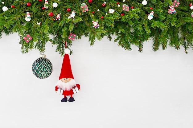 Boże narodzenie bożenarodzeniowa jedlinowa gałąź z santa i zieloną bożenarodzeniową piłką na białym drewnianym tle. copyspace, widok z góry