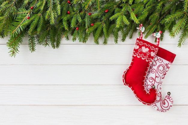 Boże narodzenie bożenarodzeniowy jedlinowy drzewo, czerwone bożenarodzeniowe skarpety na białym drewnianej deski tle z kopii przestrzenią.