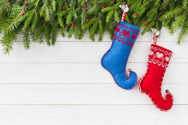 Boże narodzenie bożenarodzeniowy jedlinowy drzewo z dekoracją, czerwonymi i błękitnymi bożenarodzeniowymi skarpetami na białym drewnianej deski tle z kopii przestrzenią