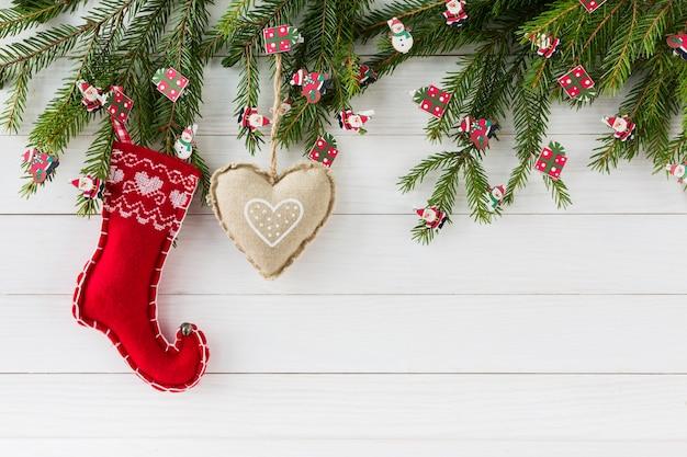 Boże narodzenie bożenarodzeniowy jedlinowy drzewo z dekoracją na białym drewnianej deski tle z kopii przestrzenią.