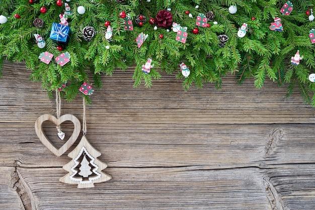 Boże narodzenie bożenarodzeniowy jedlinowy drzewo z dekoracją na starym drewnianym tle.
