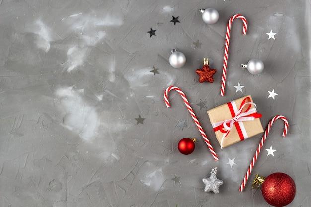 Boże narodzenie candy cane czerwone i srebrne kulki gwiazdki. koncepcja obchodów nowego roku z prezentem