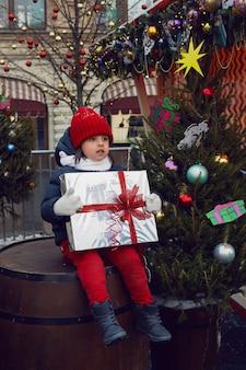 Boże narodzenie chłopiec dziecko w ciepłych ubraniach trzyma prezent i siedzi na beczce obok choinki w moskwie
