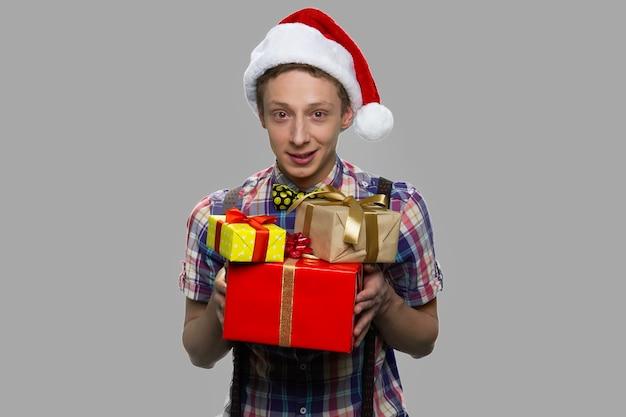Boże narodzenie chłopiec z pudełka na szarym tle. chłopiec w kapeluszu świętego mikołaja, trzymając prezenty i patrząc na kamery.