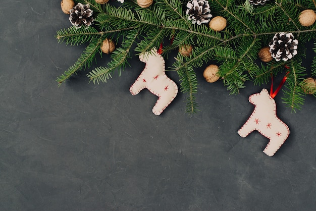 Boże narodzenie ciemne tło wakacje, naturalne dekoracje ustawione w kompozycji z ręcznie robione konie zabawki, świerkowe gałęzie, szyszki