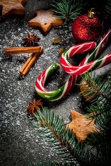 Boże narodzenie ciemne tło z gałęzi choinki, szyszki, słodycze trzciny cukrowej, prezenty, bombki i dekoracje