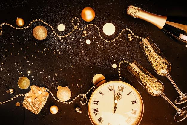 Boże narodzenie ciemne tło. złote przedmioty i ozdoby świąteczne, kieliszki, szampan, zegarki. koncepcja obchodów bożego narodzenia. płaska kompozycja z widokiem z góry.