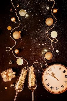 Boże narodzenie ciemne tło złote przedmioty świąteczne i ozdoby kieliszki do szampana zegarki