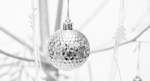 Boże narodzenie czarno-biały obraz z alternatywną choinką ze srebrnego drewna ozdobionego xmas ball bliska.