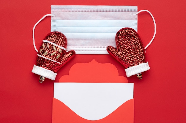 Boże narodzenie czerwona koperta list z miejscem na tekst na czerwonym tle, a także maska medyczna jako symbol bezpieczeństwa