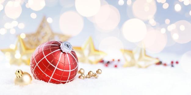 Boże narodzenie czerwona piłka z dekoracją na śniegu.
