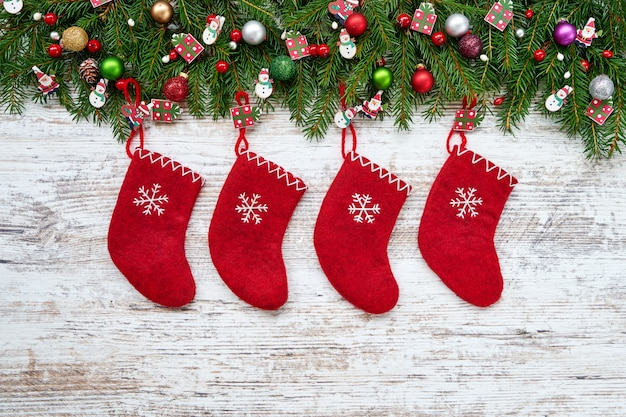 Boże narodzenie czerwone bożenarodzeniowe skarpety na białym drewnianym tle z bożenarodzeniowym jedlinowym drzewem.
