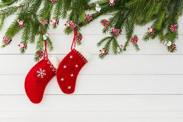 Boże narodzenie czerwone bożenarodzeniowe skarpety na białym drewnianym tle z dekorującym bożenarodzeniowym jedlinowym drzewem. skopiuj miejsce