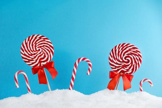 Boże narodzenie czerwone cukierki laski i lizaki w śniegu na niebieskim tle. wesołych świąt bożego narodzenia słodycze