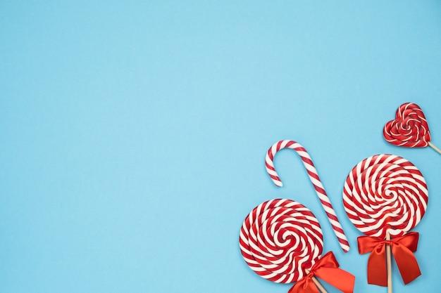 Boże narodzenie czerwone paski cukierki laski i lizaki na niebieskim tle