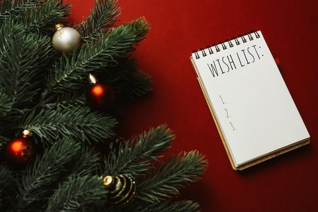 Boże narodzenie czerwone tło z pustym notatnikiem z listą życzeń, piórem, gałęziami jodły i czerwonymi dekoracjami.