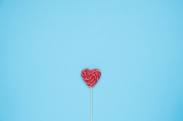 Boże narodzenie czerwony cukierek kształcie serca na niebieskim tle