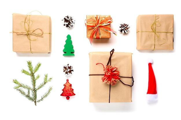 Boże narodzenie czerwony kapelusz santa, gałąź jodły, szyszki, dekoracje i prezenty na białym tle