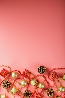 Boże narodzenie czy nowy rok różowe tło z czerwonymi i złotymi dekoracjami na choinkę z wolnego miejsca. widok z góry. nastrój noworoczny.