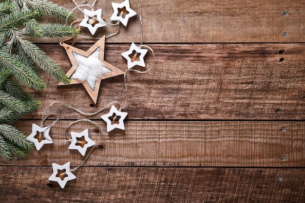 Boże narodzenie czy nowy rok tło z gałęzi jodły, garland, bombki, pudełko, drewniane płatki śniegu i gwiazdy na ciemnym tle drewnianych. miejsce na twój tekst