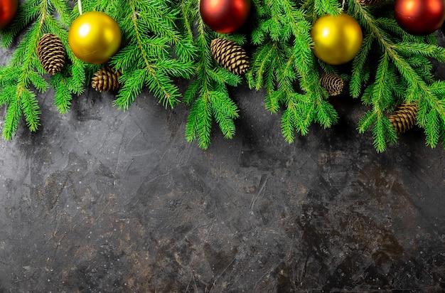 Boże narodzenie czy nowy rok tło z jodły, ozdoby świąteczne i wypukłości na ciemnej czarnej tablicy