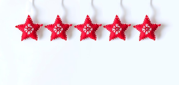 Boże narodzenie czy nowy rok tło z wystrojem. czerwone miękkie gwiazdki z haftem na białym tle