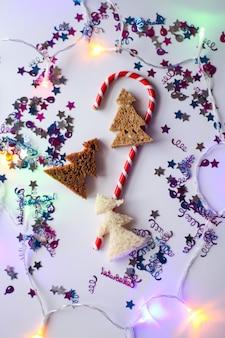 Boże narodzenie czy nowy rok uroczysty tło. kartka z życzeniami z cukierkami w paski, brokatami i jodłami z chleba. koncepcja wakacji.