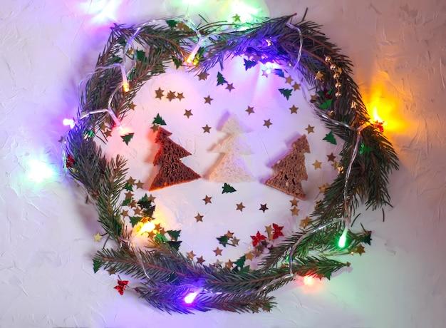 Boże narodzenie czy nowy rok uroczysty tło. kartka z życzeniami z zielonym wieńcem, kolorowymi girlandami świateł, brokatami i choinkami z chleba. koncepcja wakacji.