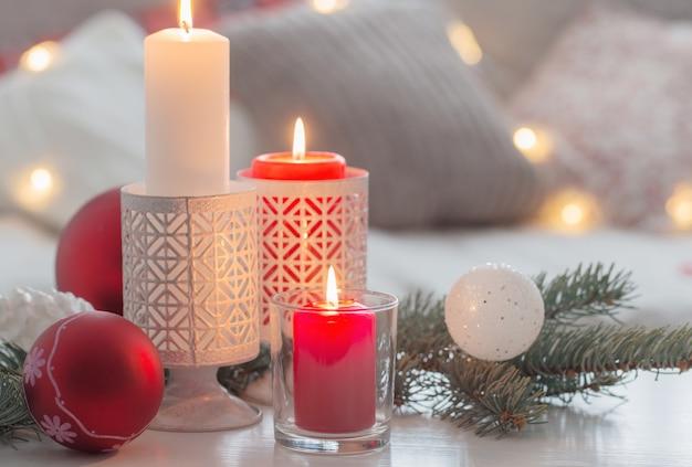 Boże narodzenie decora ze świecami i kulkami na białym stole wewnątrz
