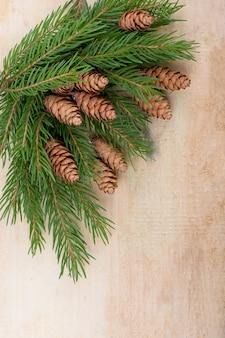 Boże narodzenie dekoracyjne rustykalne ramki z gałązek świerkowych i szyszek na ciemnym tle drewnianych, miejsce na tekst