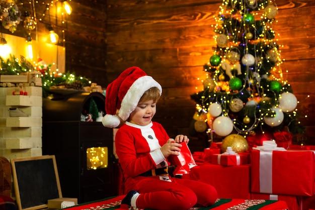 Boże narodzenie dla dzieci. szczęśliwe małe dziecko ma na sobie ubrania świętego mikołaja, bawiąc się świątecznym pudełkiem otoczonym prezentami świątecznymi.
