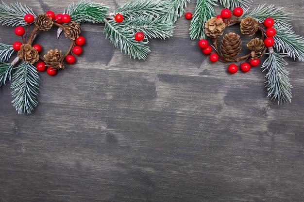 Boże narodzenie drewniane tła z choinką i czerwonymi dekoracjami. boże narodzenie wieniec z rustykalnym tle drewna.