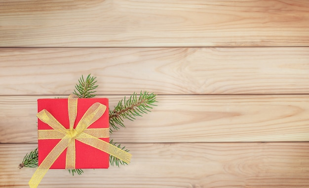 Boże narodzenie drewniane tło z czerwonym pudełkiem i gałęzią choinki