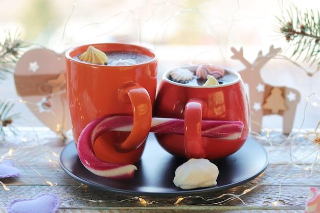 Boże narodzenie dwie filiżanki kawy z bezami gałązki jodły karmelowej tło okna
