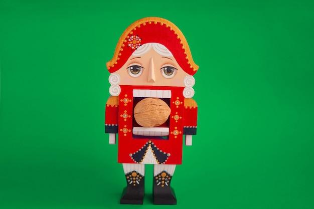Boże narodzenie dziadek do orzechów zabawka żołnierz w czerwonej tradycyjnej postaci, na zielonym tle.
