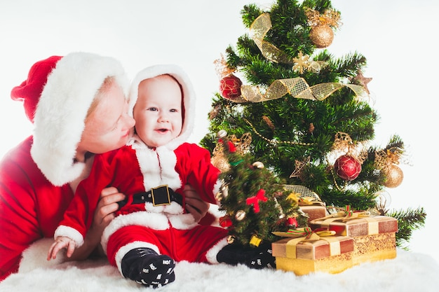 Boże narodzenie dziecko i mama pod jodłą na białym tle