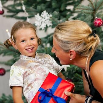 Boże narodzenie, dziecko otrzymujące prezent