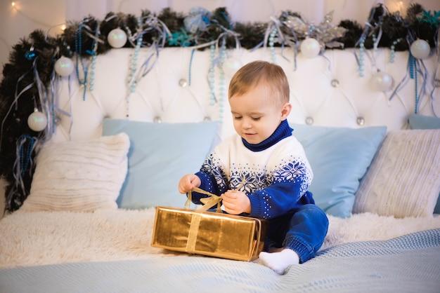 Boże narodzenie dziecko otwarty prezent prezent, szczęśliwy chłopiec patrząc na magiczne pudełko.